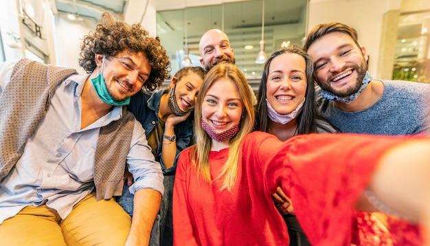 Группа друзей в масках для лица, делающих селфи с помощью мобильного телефона в помещении