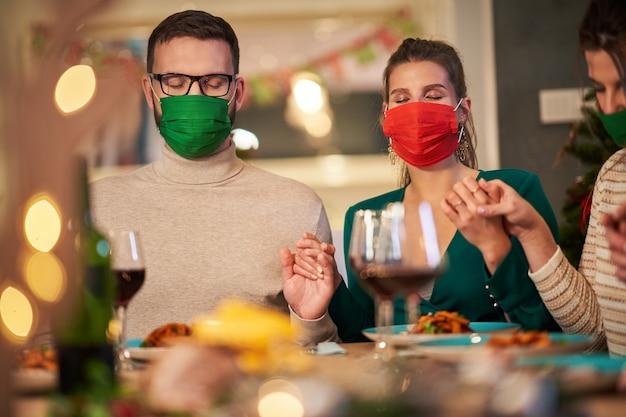 自宅で感謝祭のクリスマステーブルの上で祈るマスクを身に着けている友人のグループ