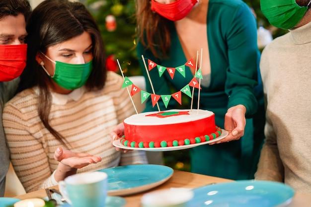X-massケーキを楽しんでいる家でクリスマスを祝っている間保護マスクを身に着けている友人のグループ