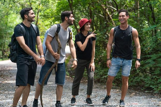 森の中で一緒に歩いて笑ったバックパック幸せな楽しい友達のグループ