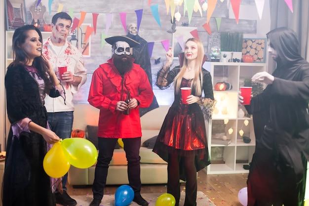 ハロウィーンの衣装を着て踊ったり笑ったりしている友達のグループ。