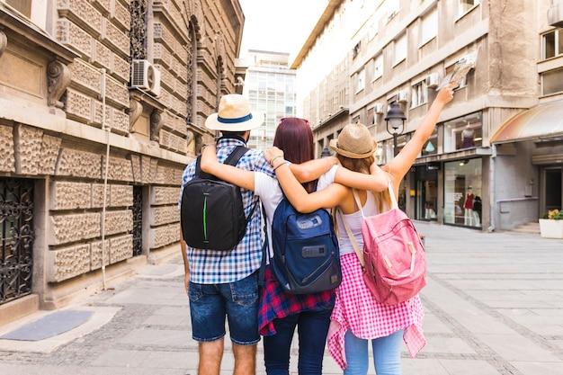 リュックサックが通りに立っている友人のグループ