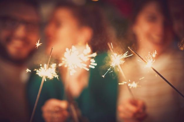 家でクリスマスと新年を祝う線香花火と友達のグループ