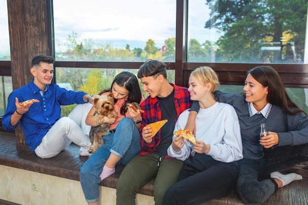 Группа друзей, молодых счастливых с собакой, едящей пиццу, сидя на окне в доме