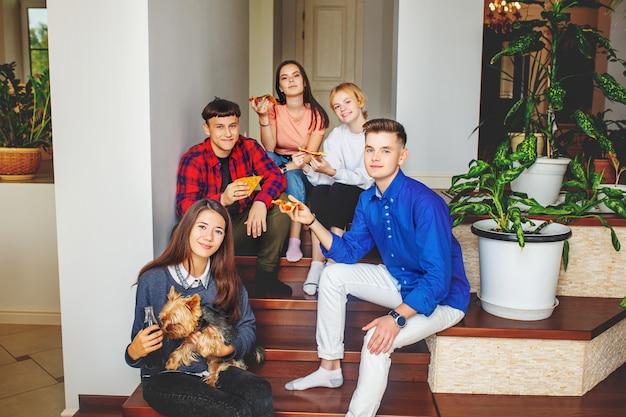 Группа друзей, молодых счастливы с собакой, едящей пиццу, сидя на лестнице в помещении