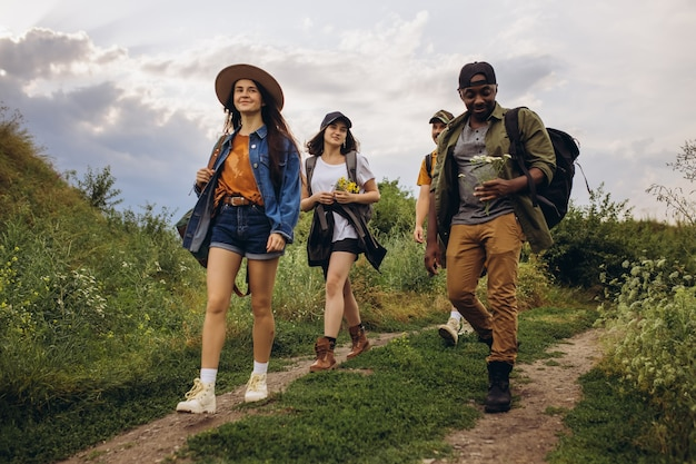 Группа друзей, молодые мужчины и женщины гуляют, гуляют вместе во время пикника в летнем лесу