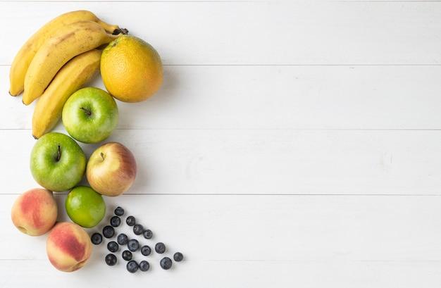 コピースペースと白い木製のテーブルの上の果物のグループ。