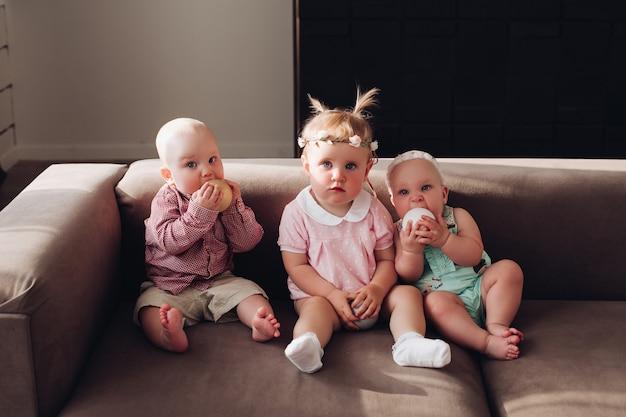 Группа забавных милых детей, сидящих вместе на диване, играя с красочными шарами. три счастливых ребенка, мальчик и девочка в цветной одежде, позируют на удобном диване в полный рост