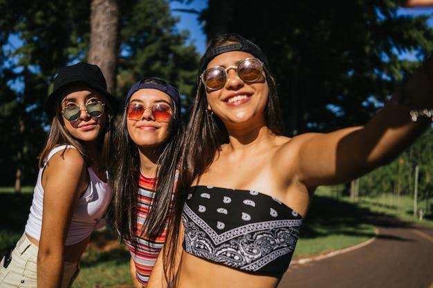 ガールフレンドのグループが公園で自分撮りをします。