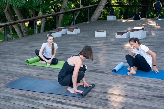 女の子のグループは、公園で朝に充電する準備をしています。女性は朝の練習のためにヨガマットをレイアウトします。