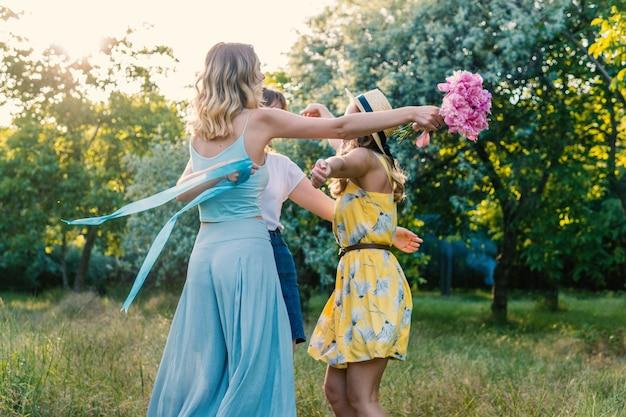 屋外でピクニックをするガールフレンドのグループ。彼らはお互いにラウンドレイを踊り、抱きしめます