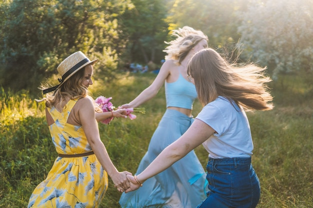 屋外でピクニックをするガールフレンドのグループ。彼らはお互いにラウンドレイを踊ります。独身パーティー