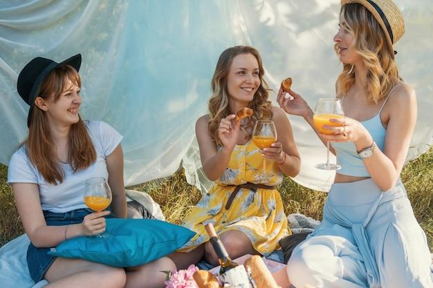 야외 피크닉을 만드는 여자 친구의 그룹입니다. 그들은 크로와상으로 서로를 먹입니다.