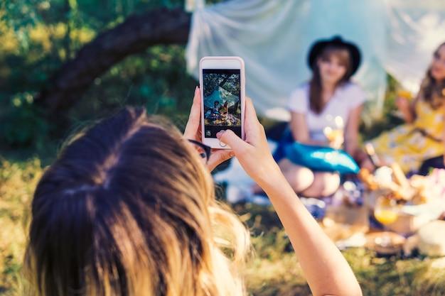 屋外でピクニックをするガールフレンドのグループ。彼らはスマートフォンから写真を作ります