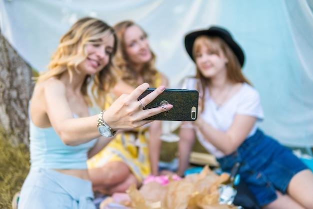 屋外でピクニックをするガールフレンドのグループ。彼らはスマートフォンから自分撮り写真を作ります。独身パーティー