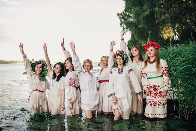Группа девочек, одетых в традиционную одежду и стоящих в воде