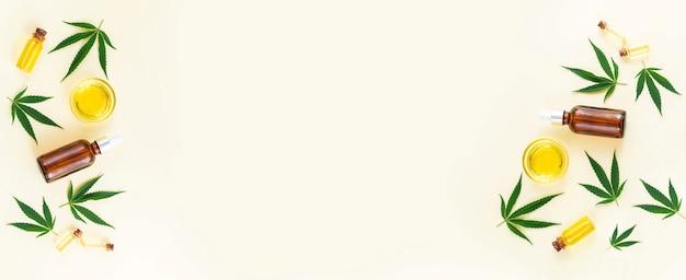 Группа стеклянных бутылок, капельницы и миски с маслом cbd каннабиса, настойкой thc и листьями конопли. вид сверху, плоская планировка, баннер с копией пространства