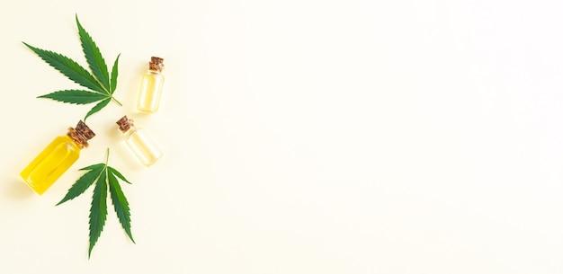 Группа стеклянных бутылок с маслом cbd конопли, настойкой thc и листьями конопли. вид сверху, плоская планировка