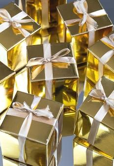 反射と灰色の背景にゴールドの輝くギフトボックスのグループ
