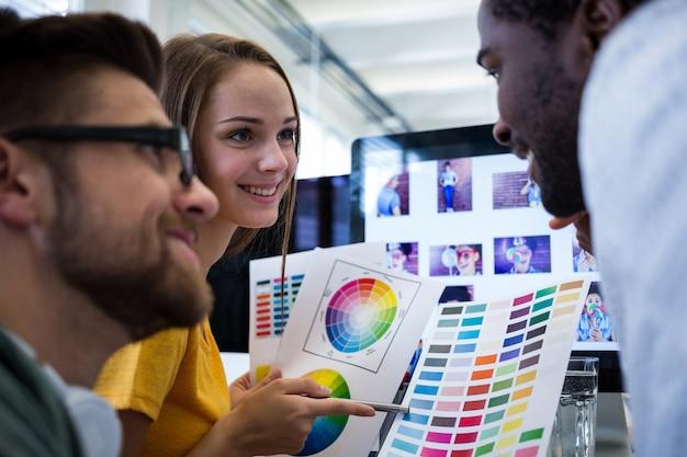컬러 차트에서 색상을 선택하는 그래픽 디자이너 그룹