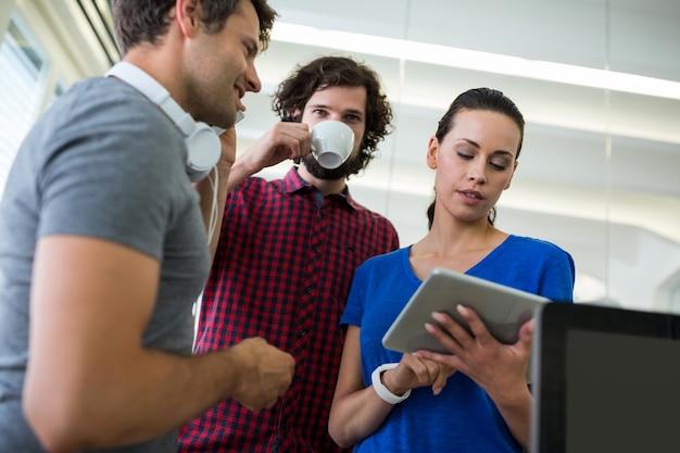 커피를 마시면서 디지털 태블릿을 사용하는 그래픽 디자이너 그룹