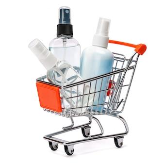 白いテーブルの上の小さなショッピングカートバスケットの手の消毒スプレーと液体石鹸ボトルのグループ