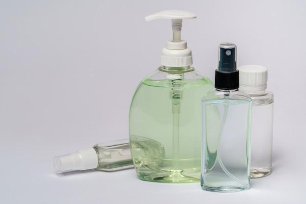ライトグレーのテーブルの上の手の消毒スプレーまたは液体石鹸ボトルのグループ