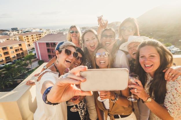 幸せで陽気な若い女性のグループは、電話で自分撮り写真を撮る屋外で一緒にパーティーで楽しんでいます