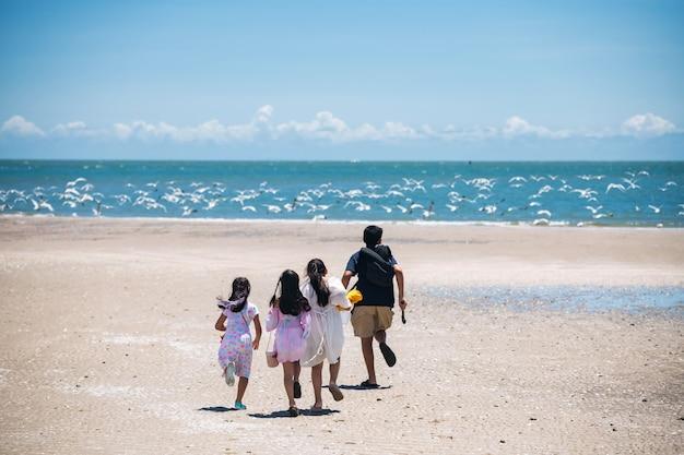 幸せなアジアの子供たちのグループが砂浜を走り、多くの白い茶色の頭のカモメが飛び去ります。熱帯の国の青い空を背景に夏の海の海岸で幸せな家族の休暇。