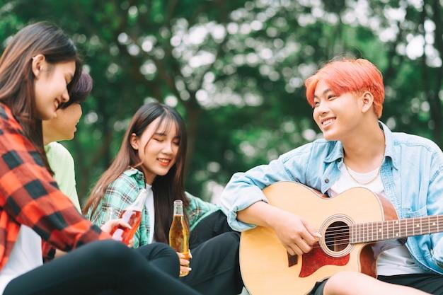기타에 앉아 공원에서 노래하는 행복 아시아 젊은 사람들의 그룹