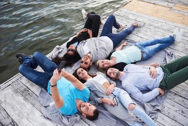 桟橋で村をやっている幸せな美しい若い人々のグループ