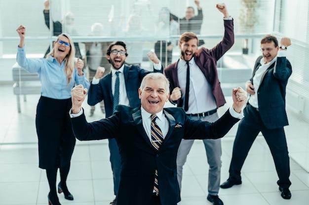 Группа счастливых деловых людей, ликуя в офисе Premium Фотографии