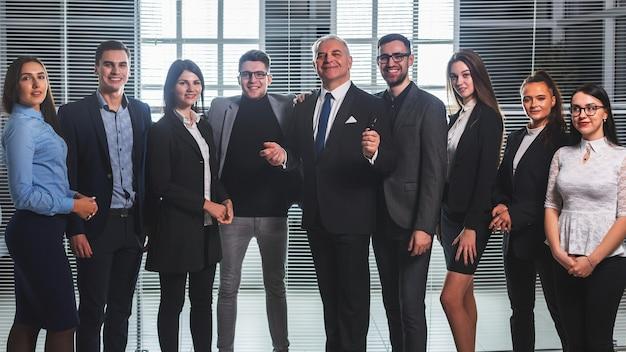 オフィスのロビーに立っている幸せなビジネスマンのグループ。成功した仕事の概念
