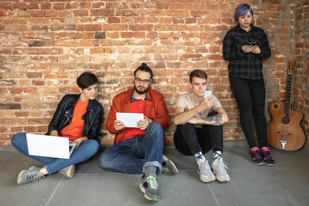 レンガの壁の後ろに幸せな白人の若者のグループ。
