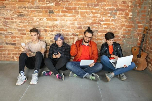 Группа счастливых кавказских молодых людей, сидящих за кирпичной стеной.