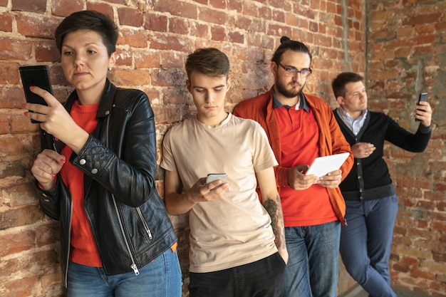 レンガの壁の後ろに立っている幸せな白人の若者のグループ。スマートフォンやタブレットからのニュース、写真、ビデオの共有、ゲームのプレイ、楽しみ。ソーシャルメディア、最新テクノロジー。