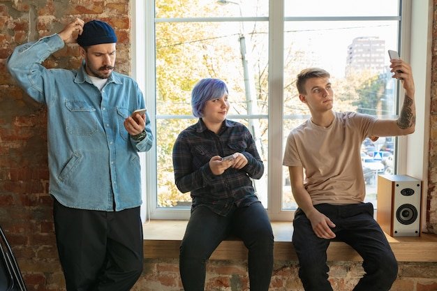 窓の後ろに立っている幸せな白人の若者のグループ。スマートフォンからのニュース、写真、ビデオの共有、自撮り写真の作成、ゲームのプレイ、楽しみ。ソーシャルメディア、最新テクノロジー。