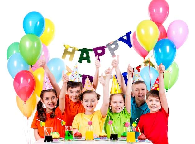 誕生日パーティーで楽しんでいるカラフルなシャツを着た幸せな子供たちのグループ-白で隔離
