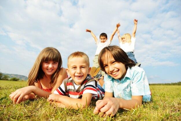 自然の中で夏の草の牧草地で幸せな子供たちのグループ