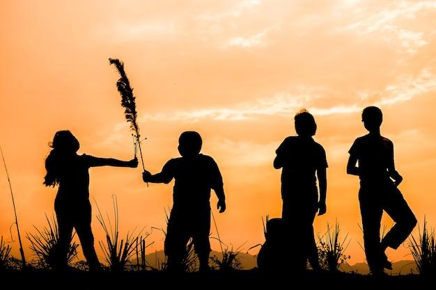 일몰, 실루엣 초원에서 놀고 행복한 아이들의 그룹