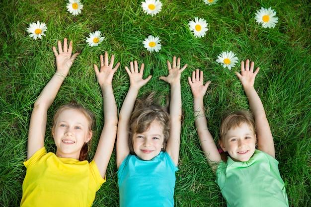 잔디에 누워 봄 공원 친구에서 재미 야외에서 아이를 재생하는 행복 한 어린이의 그룹