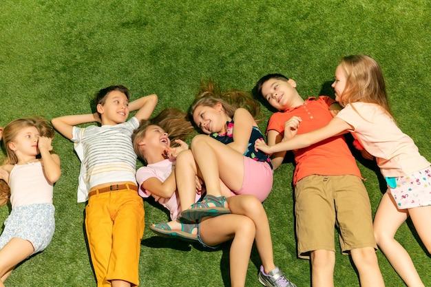 屋外で遊ぶ幸せな子供たちのグループ。春の公園で楽しんでいる子供たち。緑の芝生の上に横たわっている友達。トップビューポートレート