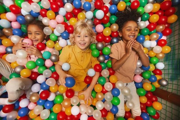 Группа счастливых детей, улыбаясь вперед, лежа среди цветных шаров в бассейне