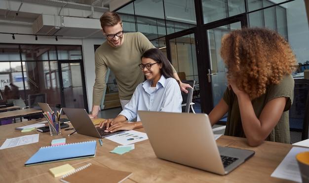 Группа счастливых коллег многорасовой бизнес-команды, работающей, сидя в современном коворкинг-пространстве