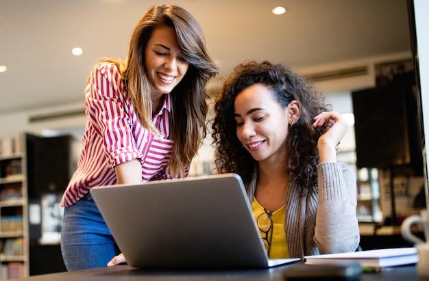 Группа счастливых студентов колледжа, обучающихся в школьной библиотеке