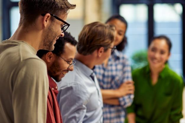 現代のオフィスで一緒に立っている幸せで多様な多民族のビジネスマンのグループと