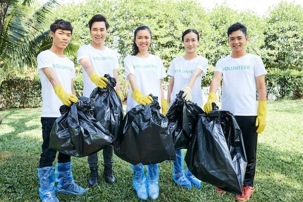 수집한 쓰레기 봉투를 들고 공원에 서 있는 행복한 자원봉사자 그룹