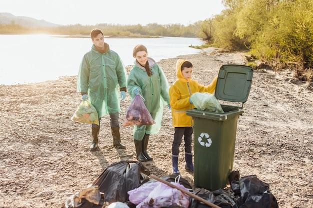 湖の近くの公園のゴミ袋の清掃エリアで幸せな家族のボランティアのグループ