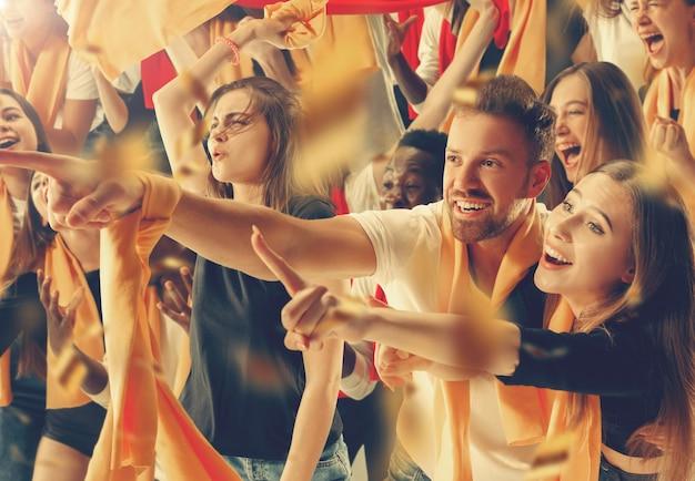 幸せなファンのグループがチームの勝利を応援しています