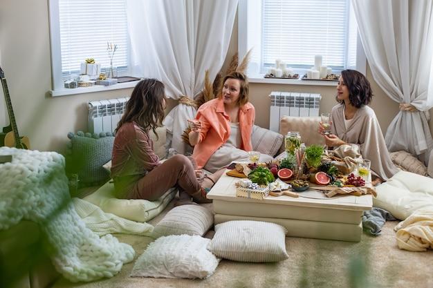 Группа счастливых подруг разговаривает, расслабляясь вместе за сервировочным столом в гостиной в стиле бохо-сканди